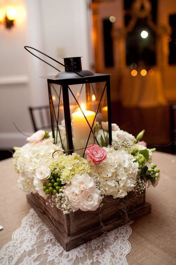 a box centerpiece with neutral florals and a candle lantern