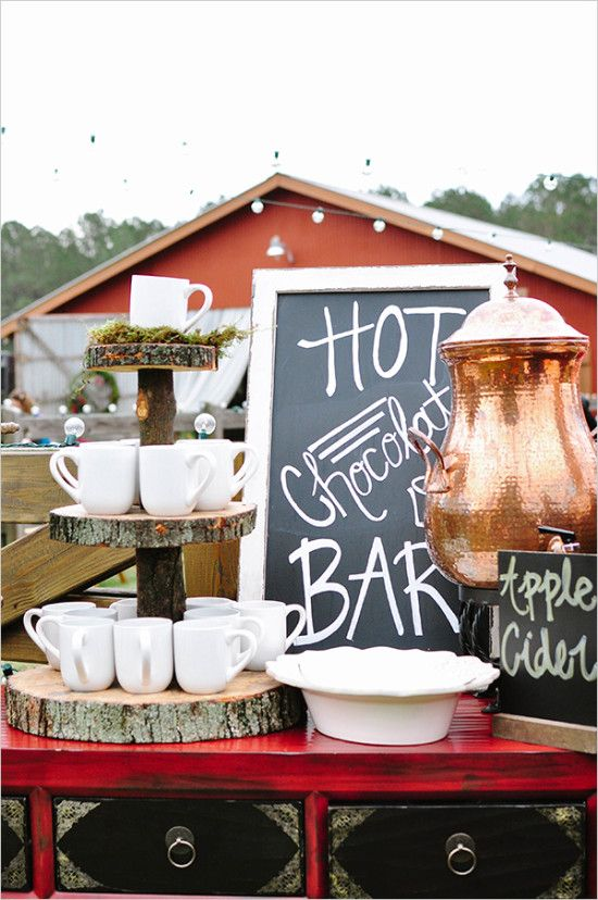 a hot chocolate bar with mugs displayed on wood slices stands is a cute fall or Christmas idea