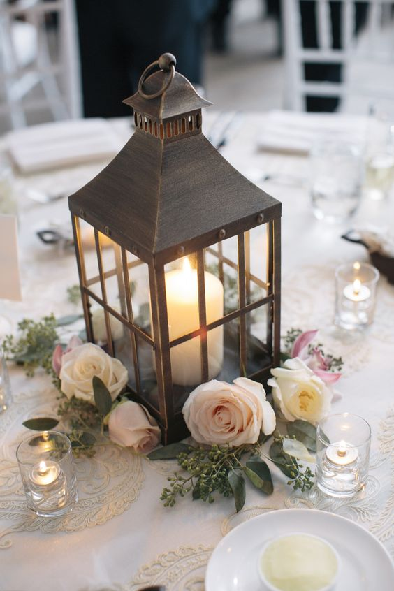 an elegant dark lantern with a candle and surrounded with roses for a chic look