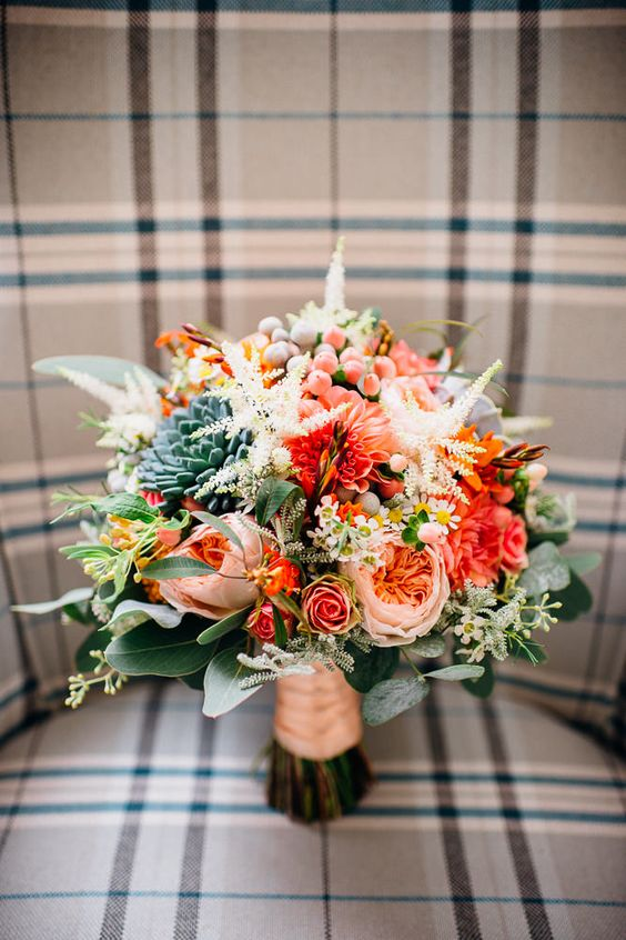 beautiful and textural wedding bouquet in peachy and orange shades and with scculents