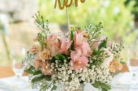 15 a bucket with a pink floral arrangement and a glitter table number