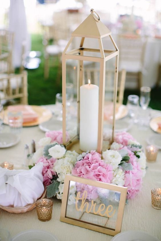 a buttermilk-colored metal lantern with pink and neutral blooms and a framed table number for a cozy backyard wedding