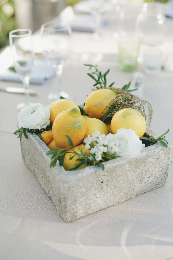 a concrete bowl with white blooms and lemons for a summer wedding centerpiece