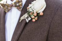 15 a tweed brown suit with a white shirt and a floral bow tie