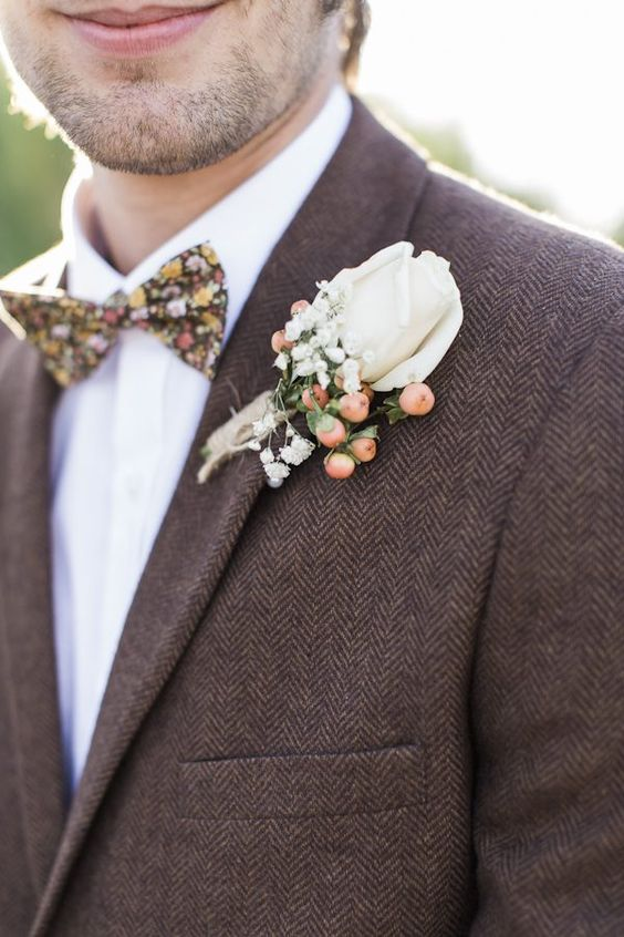 a tweed brown suit with a white shirt and a floral bow tie