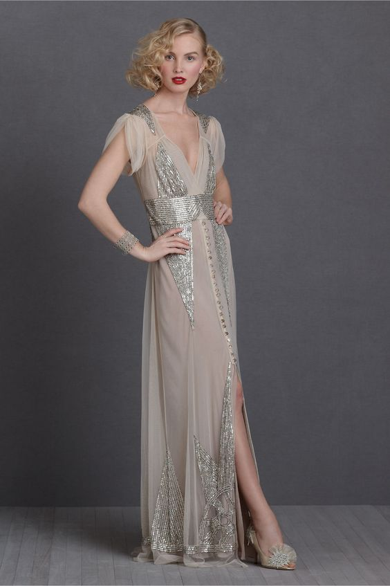 art deco inspired wedding dress with silver sequin detailing, a V cut, a bbutton row and short sleeves
