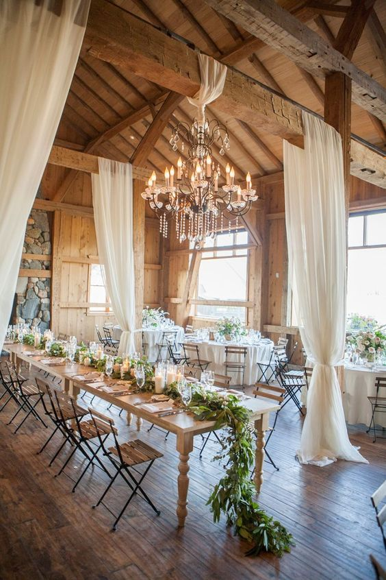 elegant wooden barn with a crystal chandelier, airy draperies and lush greenery and candles