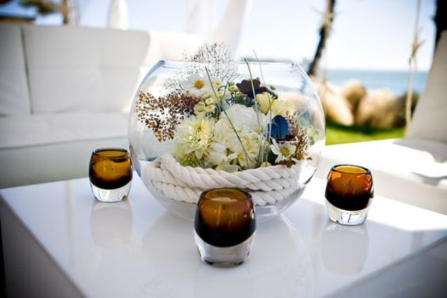 a glass bowl with rope, corals and flowers for a refined coastal wedding
