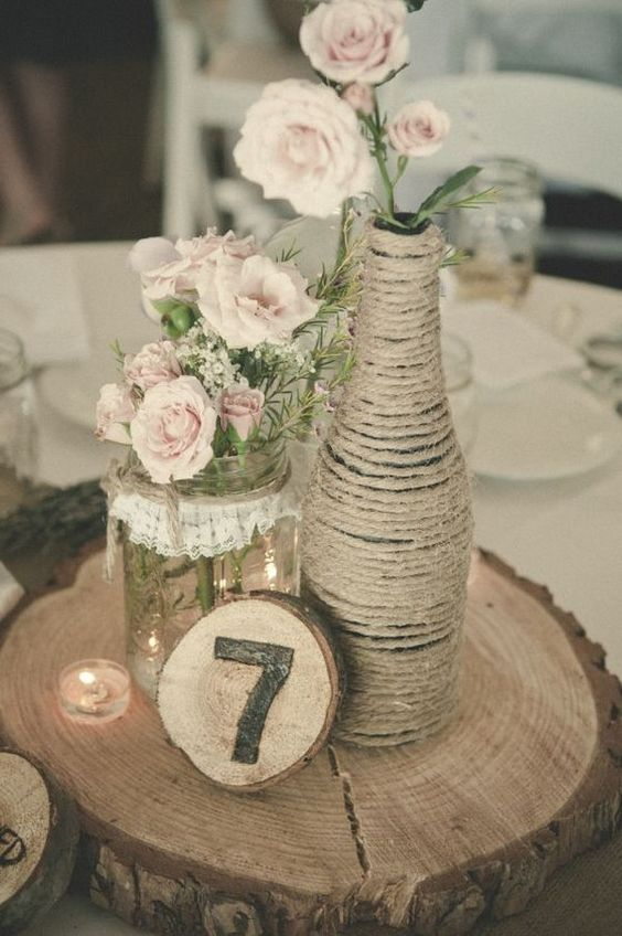 a jute wrapped bottle, a lace wrapped jar, a wood slice table number and blush roses