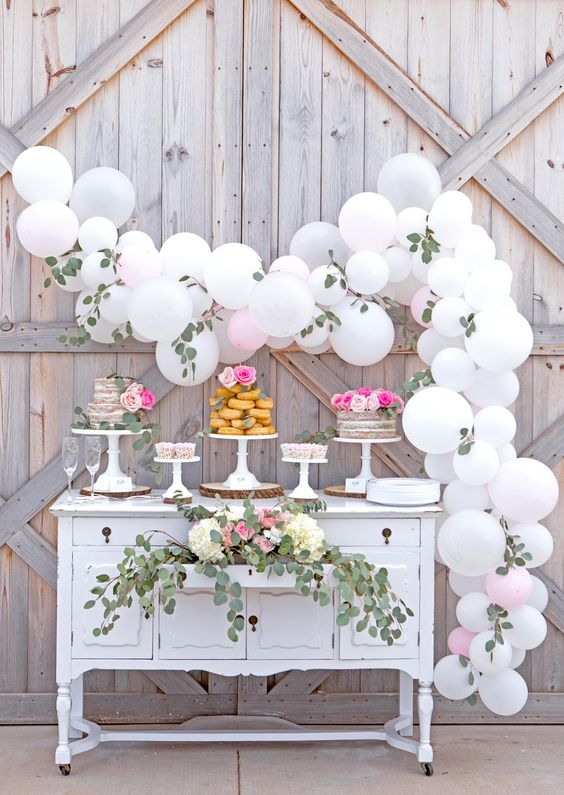 a white balloon and foliage garland over the desert table