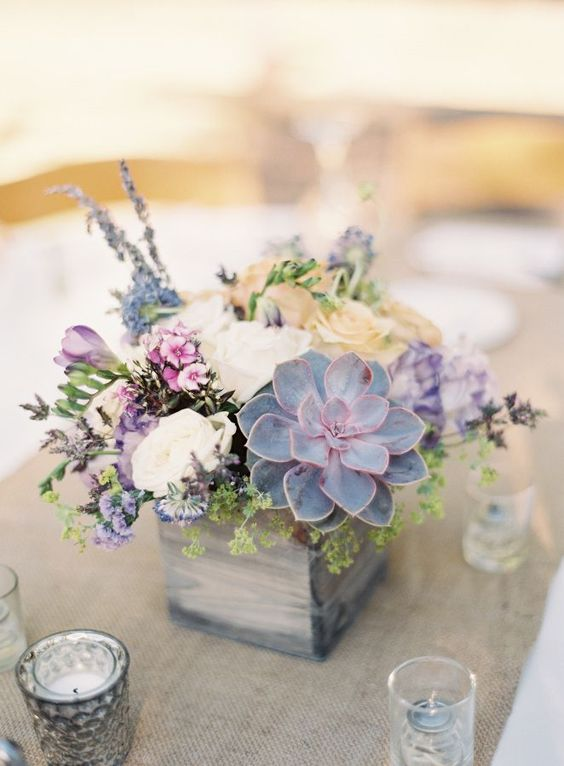 a wooden box with wildflowers and a pale succulent will be a great fit for a pastel wedding with a rustic feel