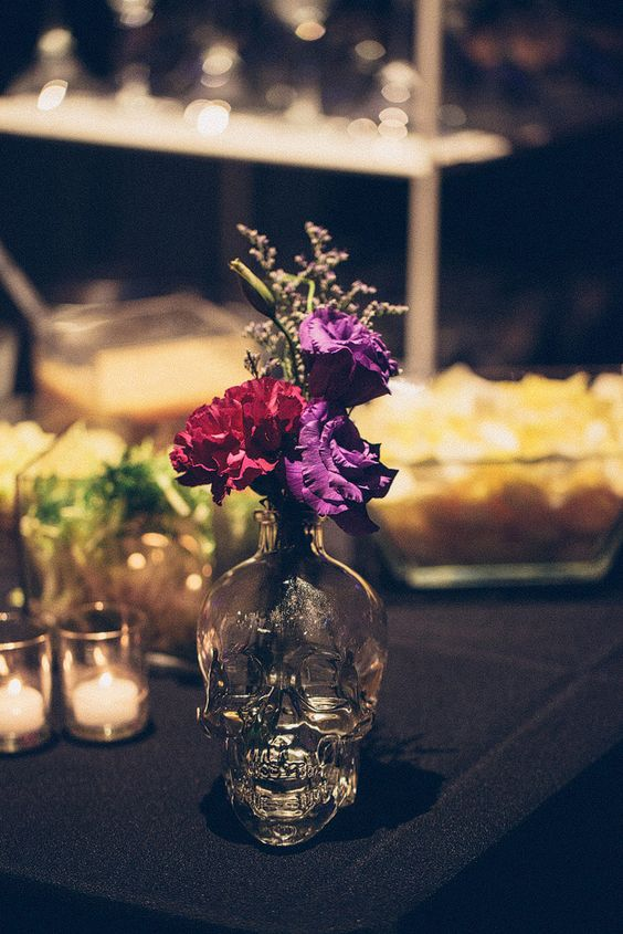 simple glass skull vases are amazing for moody weddings, just add some bold blooms