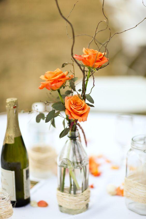 drei orange Rosen in einer Flasche umwickelt mit Garn für ein schickes Herzstück