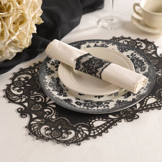 a black lace paper placemat and a black lace napkin ring match for a dramatic tablescape