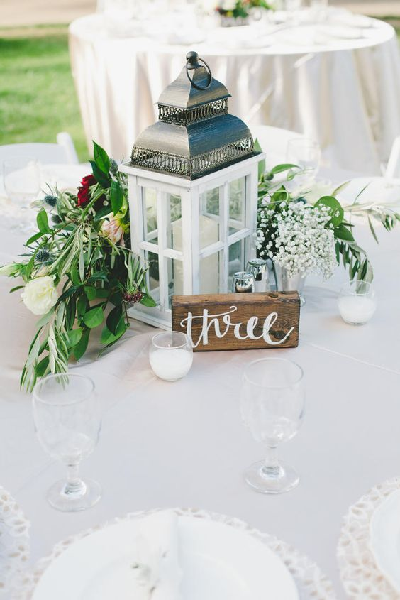 a wooden and metal candle lantern, a wooden table number and a beautiful floral and greenery arrangement