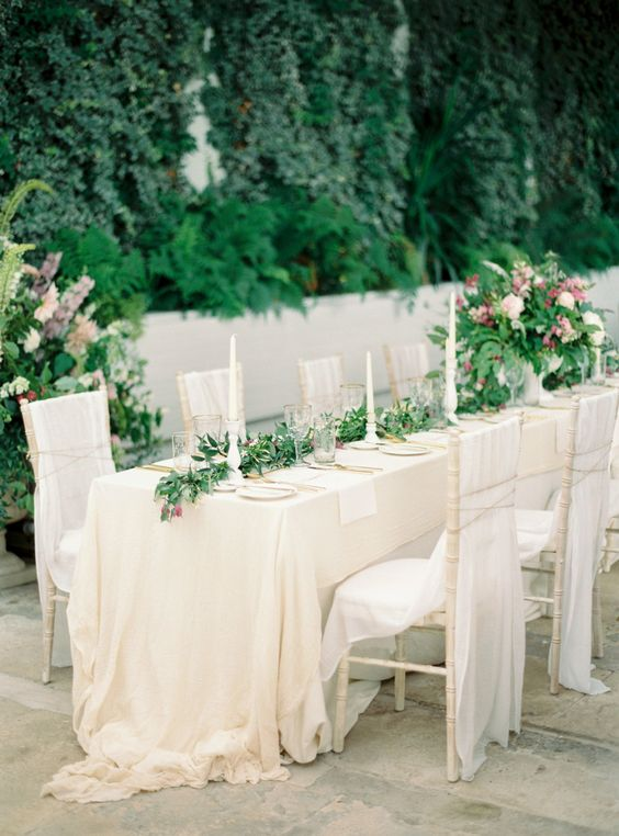 gorgeous neutral wedding reception with a greenery table garland and gold details on a castle terrace