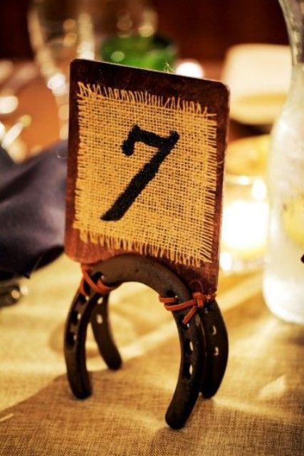 horseshoes holding burlap and leather table numbers will hint on your wedding venue