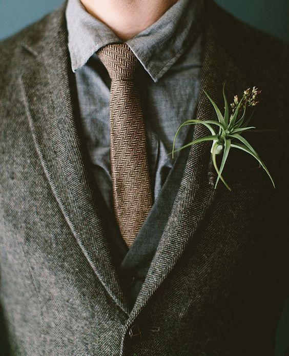 a brown tweed suit, a grey vest and shirt, a brown printed tie