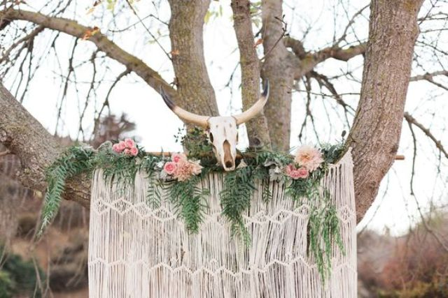 a macrame wedding backdrop with ferns, pink roses and an animal skull