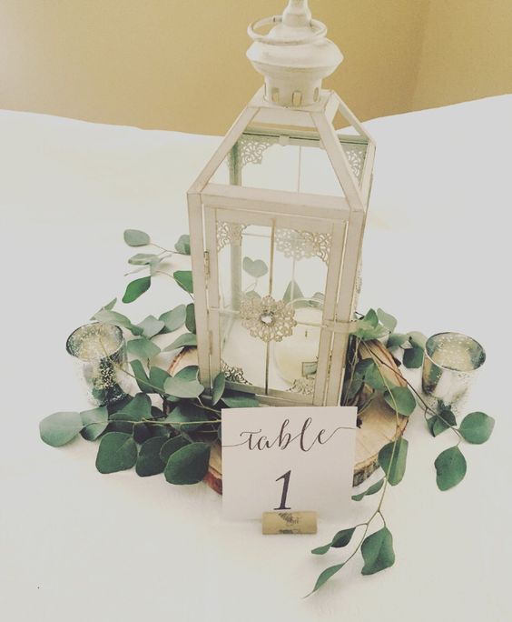 a white candle lantern on a wooden slice covered with leaves, a table number and mercury glass candle holders