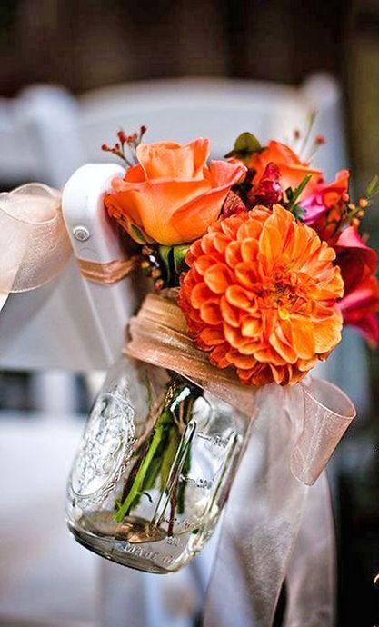 orange flower arrangement in a mason jar for wedding aisle decor