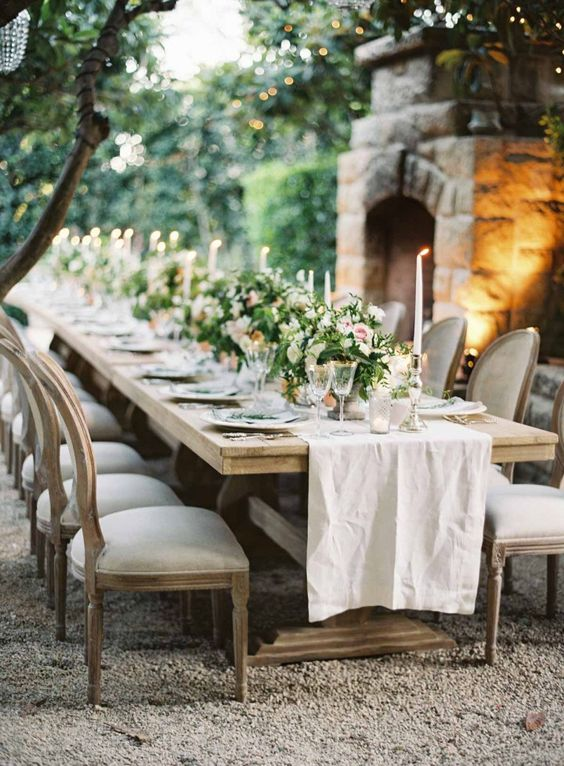 very elegant ranch wedding reception with a fireplace, lush greenery and pink flower centerpieces