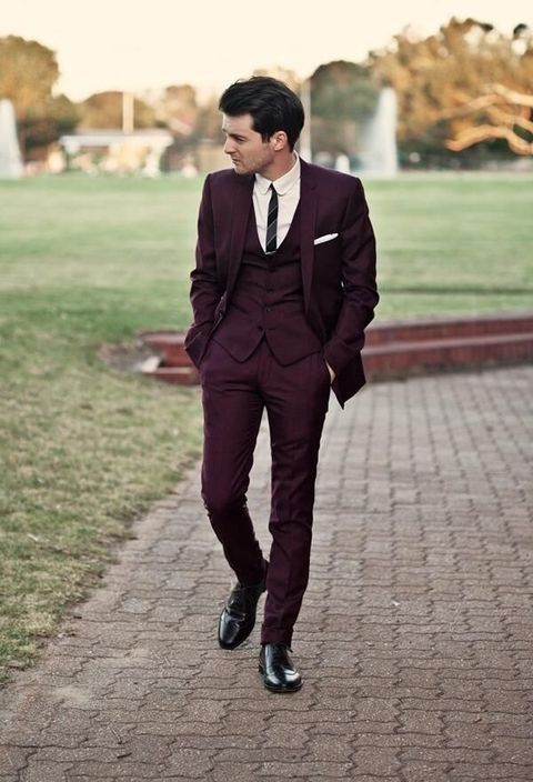 a burgundy three piece wedding suit with a thin striped tie and black shoes