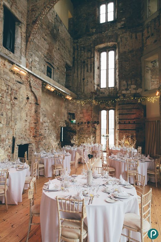 a rustic castle space with blush and gold decor for a weddign reception and lights