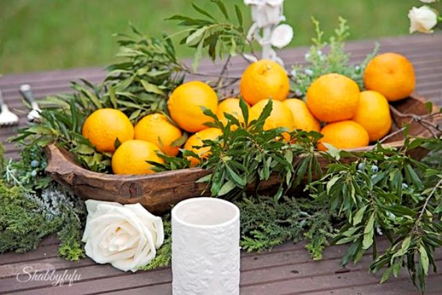 a wooden bowl with greenery and oranges for a tropical wedding