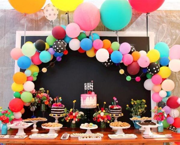 colorful balloon arch over the dessert table is a cool and chic idea
