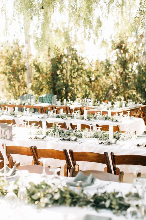 wedding reception with greenery table runners, candles and wooden chairs