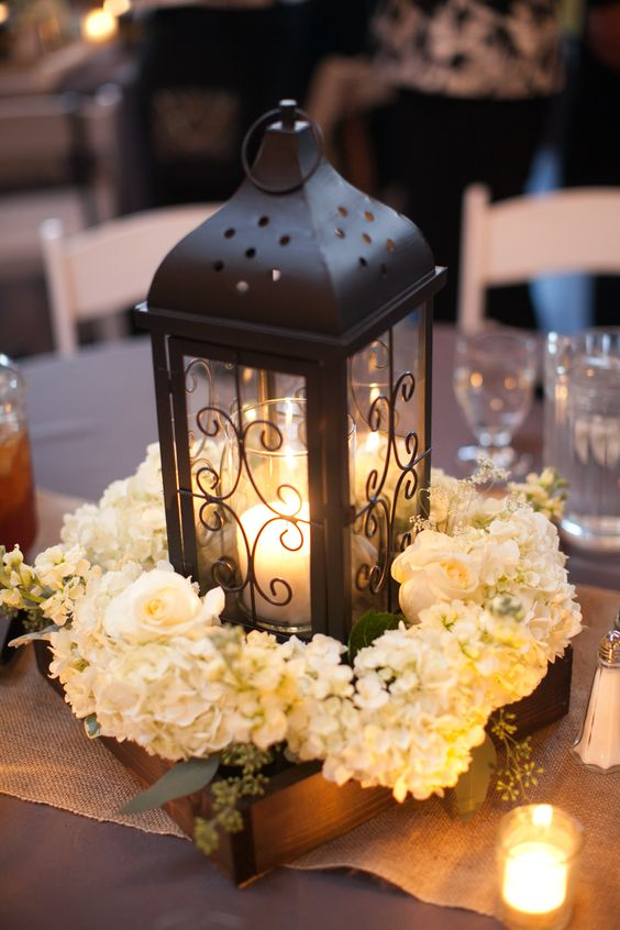 a dark metal candle lantern in a box with white floral arrangements for a rustic tablescape