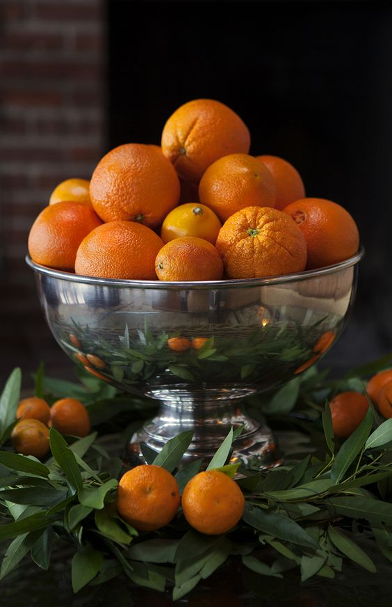 a silver bowl with oranges and tangerins for a tropical wedding