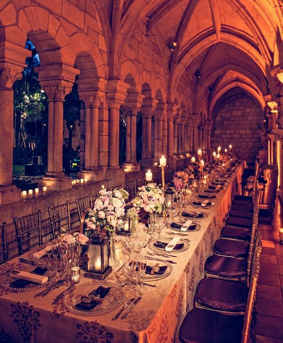 one of the castle galleries is turned into a beautiful reception space with candle lanterns, pink florals and metallic accents