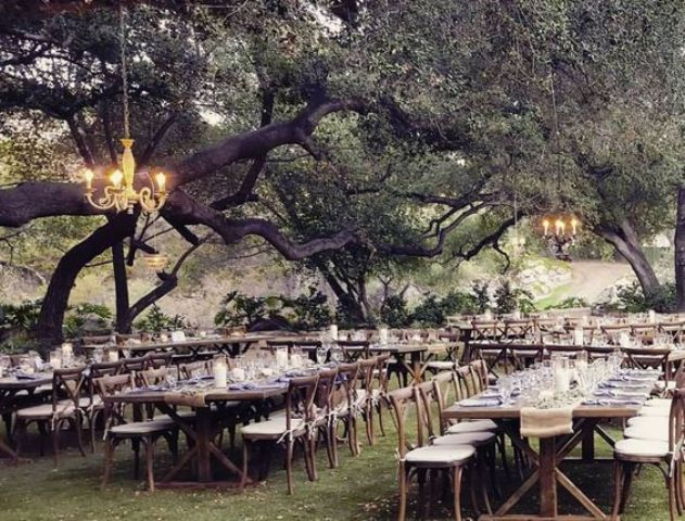 ranch wedding reception space with burlap and candle decorated tables and chandeliers