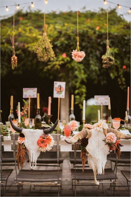 sweetheart seats decor with bold blooms and animal skulls for a boho desert wedding