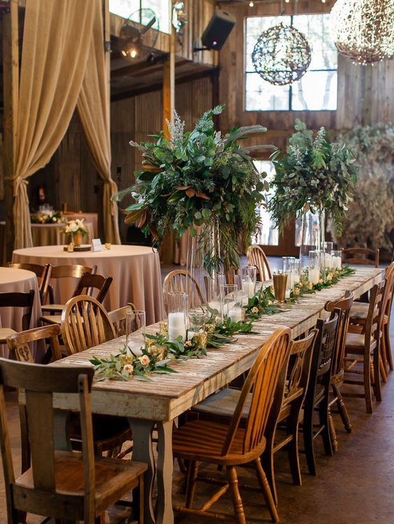 a cozy barn wedding reception with greenery, blush roeses and candles
