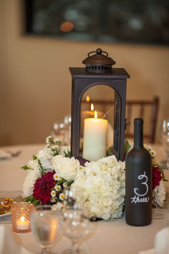 a dark metal lantern with a candle inside and a white and red bloom arrangement, a chalkboard bottle table number for a vineyard wedding