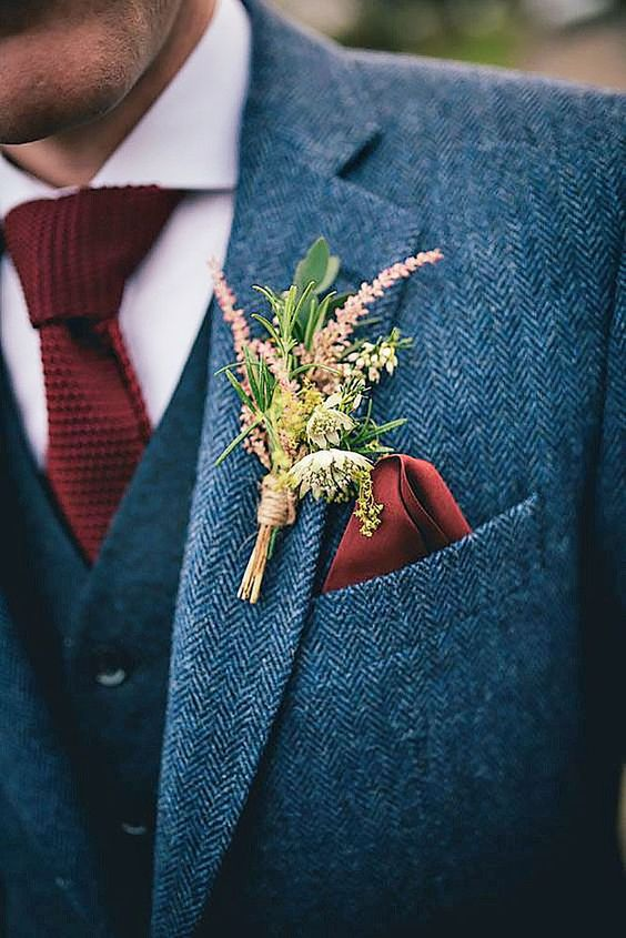 a grey tweed three piece suit with a red knit tie and a wildflower boutonniere