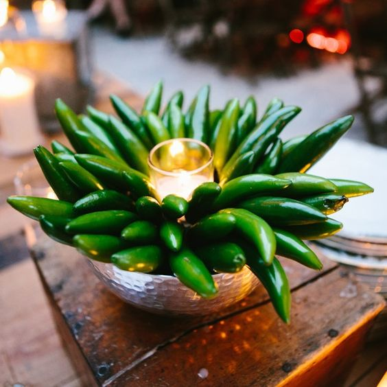 a silver bowl centerpiece with green peppers and a candle is a way to get a different look, great for fall weddings
