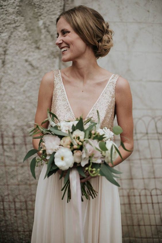 champagne-colored wedding dress with wide straps, a deep V cut and gold sequin, a plain skirt