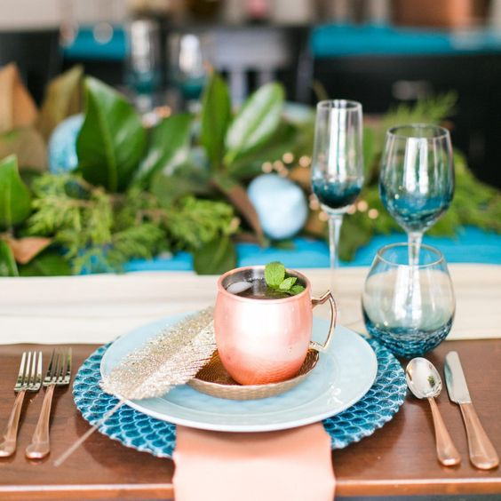 teal glasses and a charger, copper flatware, a mug and a napkin look very cool and eye-catchy together