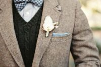 22 a light brown tweed jacket, a dark grey knit vest, a light blue shirt and a checked bow tie