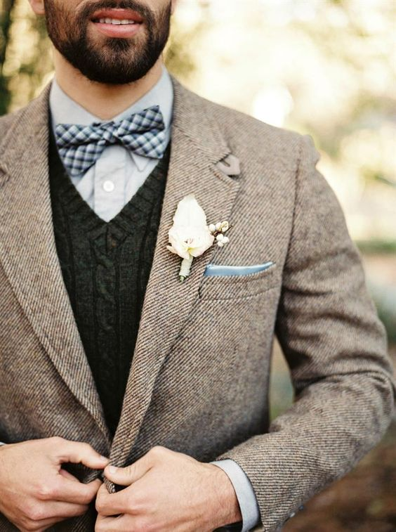 a light brown tweed jacket, a dark grey knit vest, a light blue shirt and a checked bow tie