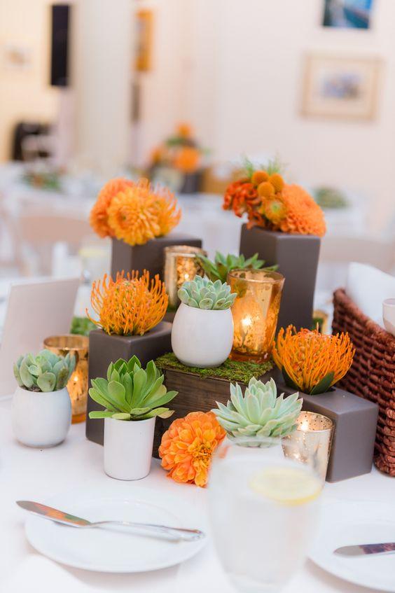 eine moderne Hochzeit Herzstück mit Sukkulenten und orange Blüten
