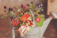22 a tin watering can with colorful flowers for a simple rustic table