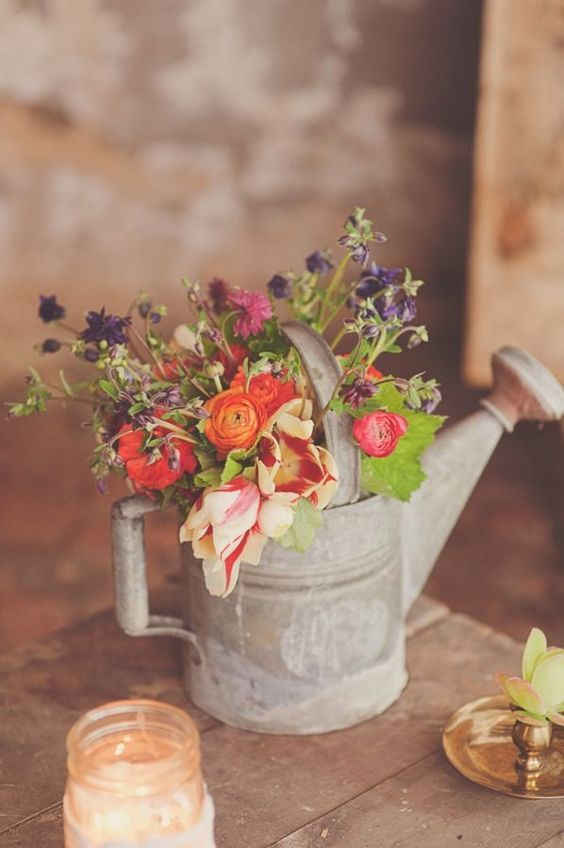 a tin watering can with colorful flowers for a simple rustic table