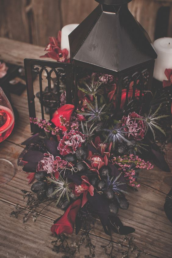 a black vintage lantern filled with red and marsala blooms, thistles and black grapes for a decadent and lux look
