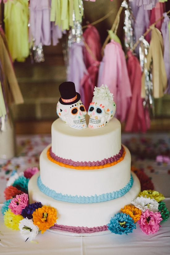 a wedding cake with colorful cream and sugar skull toppers