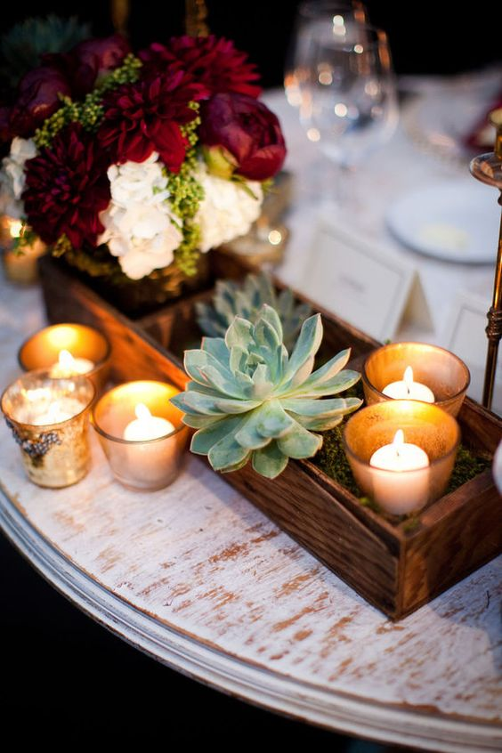 a wooden box with blooms in a jar, candles and succulents for a rustic wedding
